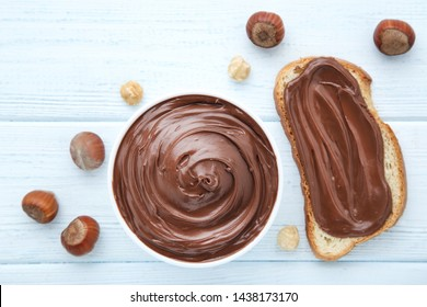 Bread with melted chocolate and hazelnuts on wooden table