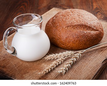 Bread and milk in a glass jar on a wooden table