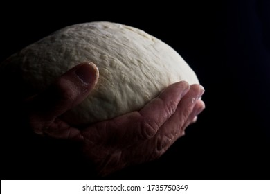 Bread in the old wrinkled hands of the grandmother close-up. Grandmother holding a piece of bread in wrinkled palms. Old woman with bread in the dark. Grandma's bread dough