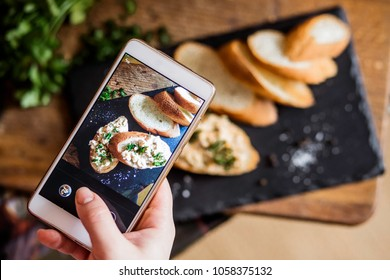 Bread on the board is photographed on the phone