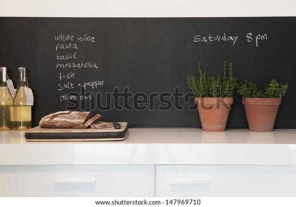 Bread on chopping board with shopping list written on blackboard in kitchen