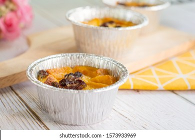 Bread pudding with black rasins in round foil cup on wooden tray. Delicious custard for coffee times.