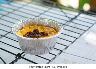 Bread pudding with black rasins in round foil cup on cake sieve. Delicious custard for coffee times.