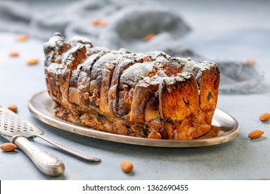 Bread pudding of buns, banana slices, cream cheese, eggs and cream sprinkled with powdered sugar on a wooden serving board, selective focus.