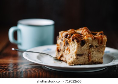 Bread pudding with caramel sauce served with a cup of hot cocoa on dark rustic background