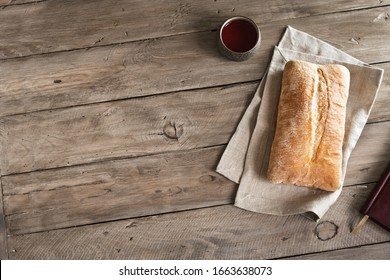 Bread and Red Wine on wooden table, copy space. Christian communion concept.