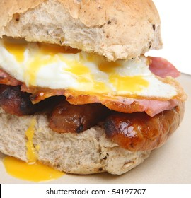 Bread roll with fried egg, bacon and sausages.