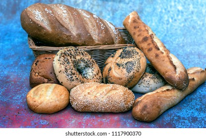 Bread and rolls assorted, with a french baguette, salted rye loaf, everything bagel, poppy seed roll and sesame seed roll