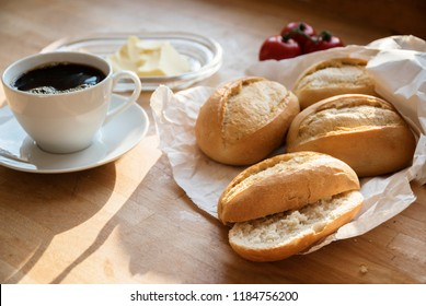 bread rolls or buns in a white paper bag, tomatoes, butter and a cup of coffee for breakfast on a wooden table, selected focus, narrow depth of field