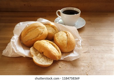 bread rolls or buns in a white paper bag and a cup of coffee on a wooden table, copy space, selected focus, narrow depth of field