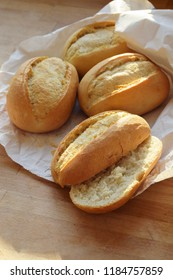 bread rolls or buns whole and halved fresh from the bakery in a white paper bag on a wooden table, vertical, selected focus, narrow depth of field