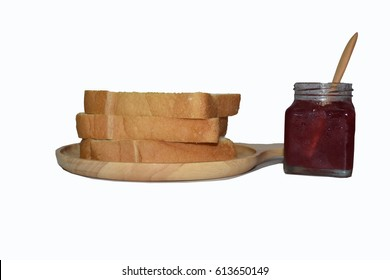 bread and rose jam on wooden plate.