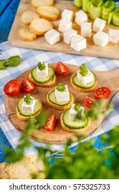 Bread rusks topped with a cube of feta cheese and cucumber slices