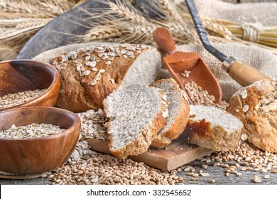 Bread from rye and healthy grains on an old rustic table with a sickle in the background