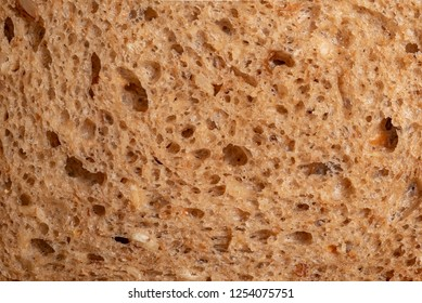 Bread with seeds and raisins as a background. Macro picture