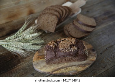 rye bread with sesame seeds and ears of rye on a wooden rustic background. With copy space for text.