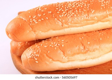 Bread with sesame seeds on a wooden board on a white background