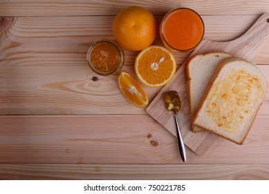 Bread set with orange jam and orange juce on wooden table.