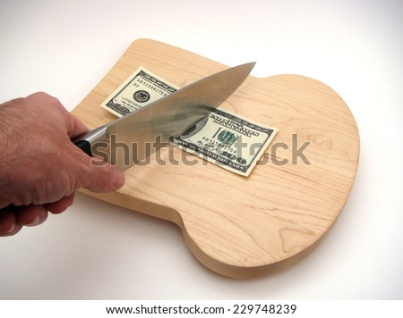 Bread Shaped Cutting Board With One Hundred United States Federal Reserve Note Obverse Side Up Under A Chef's Knife Held By Left Hand Over White Surface With Slight Vignetting.