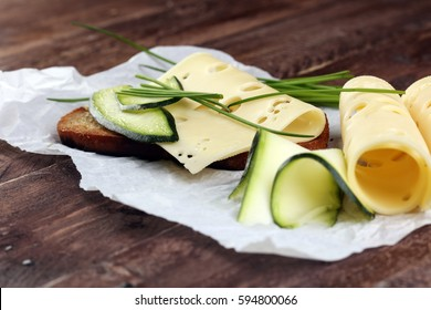Bread with slices of cheese for lunch table. Sharing antipasti on party or summer picnic time over wooden rustic background.