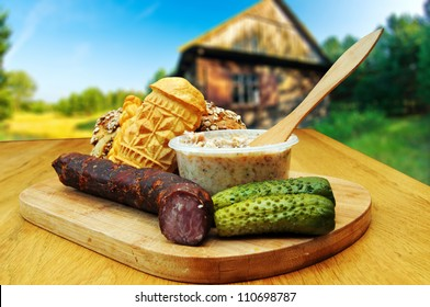 Bread, smoked cheese, kielbasa and other traditional food served outside a country cottage