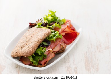 bread with smoked meat and salad on dish