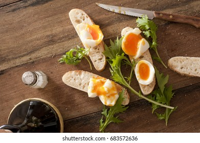 Bread soldiers with soft-boiled eggs, thin strips of toasts with greens and knife over wooden table