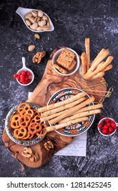 Bread Stickes, Pretzels and Cracker appetizer selection on rustic wooden board.