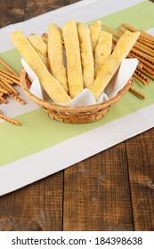 Bread sticks  in wicker basket on wooden background
