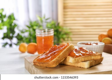 Bread with tasty apricot jam on wooden board