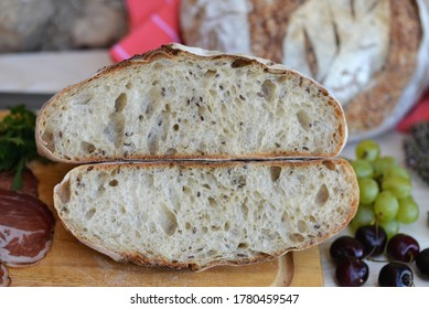Bread texture of home baked wheat sourdough bread loaf with seeds cut in half  with smoked ham, salami, grapes and cherries on wooden board; another bread loaf and herbs in background