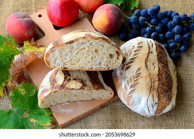 Bread texture of home baked wheat bread cut in half.  Sourdough loaf of white bread sliced on wooden board with crusty sourdough loaf on sackcloth with blue grapes, leaves and peaches in background.