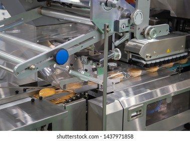 Bread, toast, bun plastic flow wrapping machine on bakery production line. Food industry