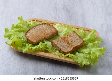 bread toast with lettuce leaf on a wooden plate