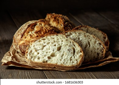 Bread, traditional sourdough bread cut into slices on a rustic wooden background. Concept of traditional leavened bread baking methods. Healthy food.