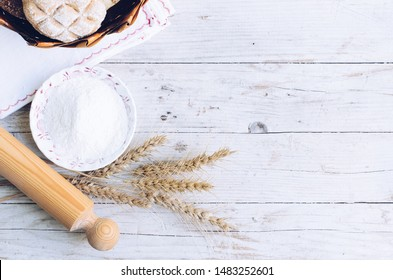 Bread with wheat ears and bowl of flour on wooden background. Rustic vintage style. Top view. Copy space.