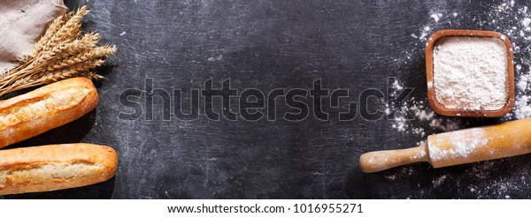bread with wheat ears and bowl of flour on dark board, top view