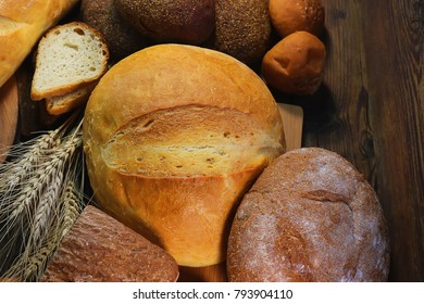 bread and wheat ears on a wooden table