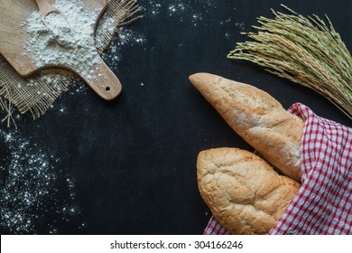 Bread , wheat and flour on black chalkboard , bakery background with free space for text