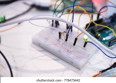 Breadboard and microcontroller with circuit and light sensor. STEAM and coding activity for kids aimed to control a green led light according with a photoresistor