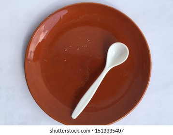 Breadcrumbs and spoon on empty brown plate.