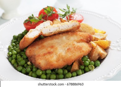 Breaded chicken breast steak with roasted potato and green peas