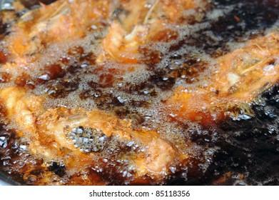Breaded chicken deep frying in oil in a cast iron frying pan