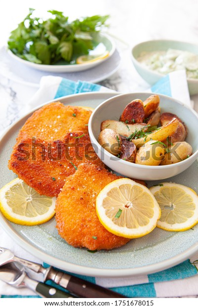 Breaded chicken schnitzel with baked potatoes and cucumber salad
