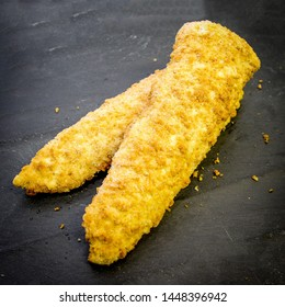 Breaded Cod or Haddock fillet of fish on a black slate with crumbs