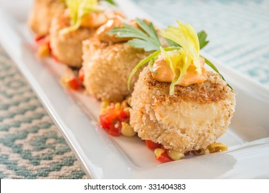 Breaded crab cakes served on top of corn relish and topped with sauce