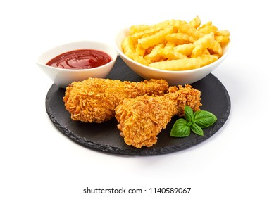 Breaded crispy chicken legs with french fries and ketchup, isolated on white background.