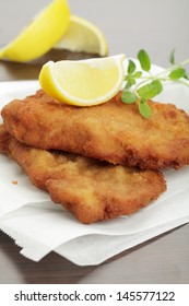 Breaded cutlet with lemon wedges