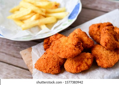 Breaded  deep fried Chicken nuggets  and  home made french fries potatoes on wooden background