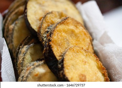 Breaded eggplant on plate with paper and being served